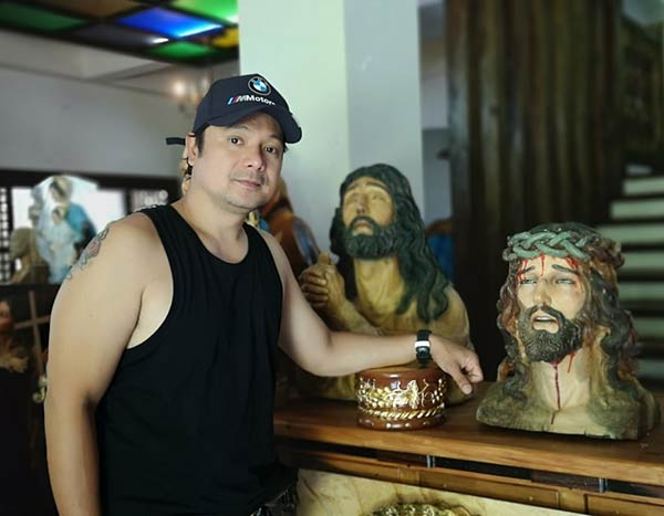 Leandro Baldemor with his wooden religious sculptures