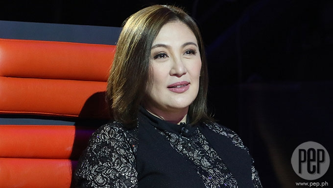 Why doesn't Sharon Cuneta want to come home yet?